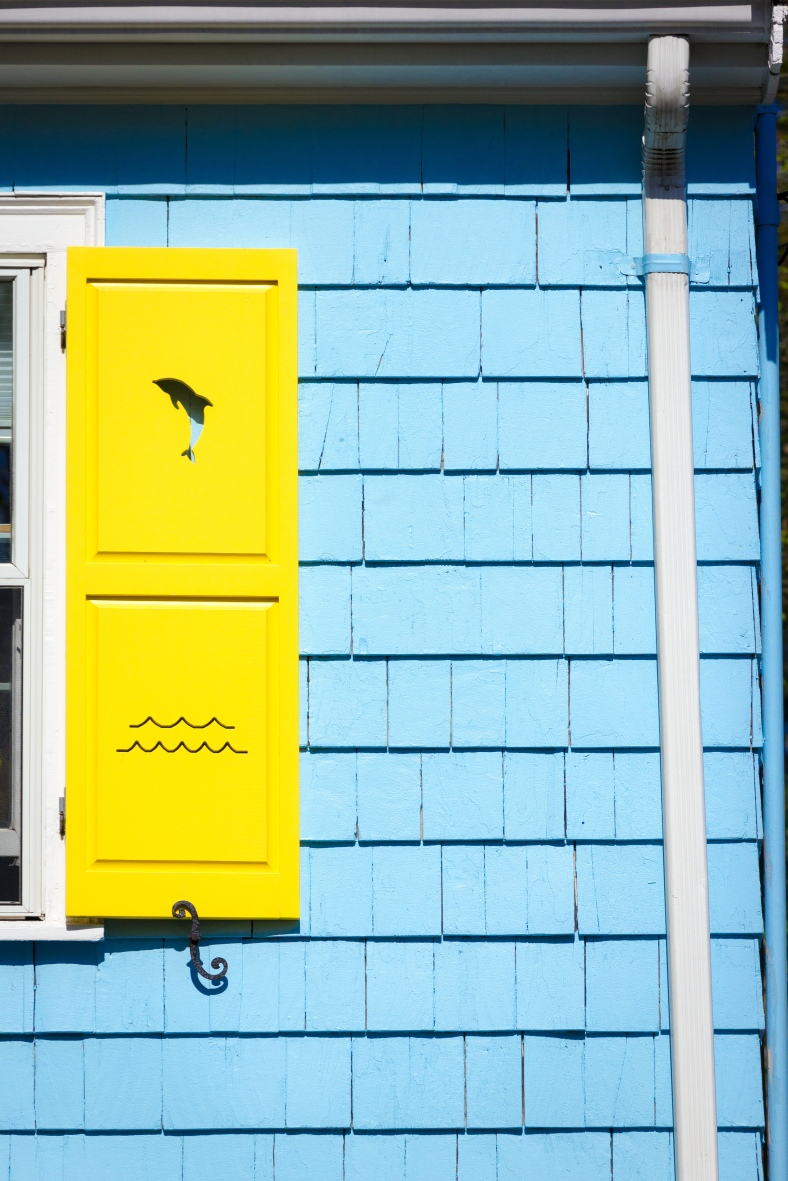 Cutouts of dolphins and waves on the colorful shutters of a Ridge Street home. May 12, 2014.