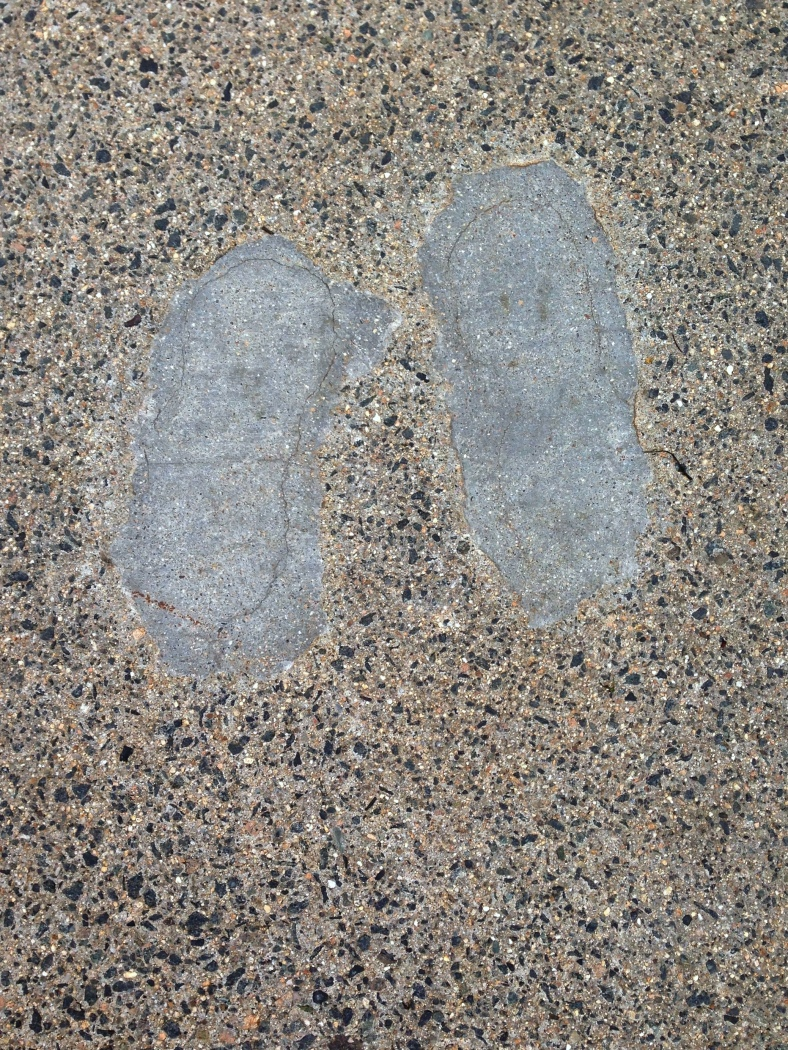 The repaired footprints of someone who decided it was a good idea to stand in wet cement, found along Massachusetts Avenue. May 13, 2014.