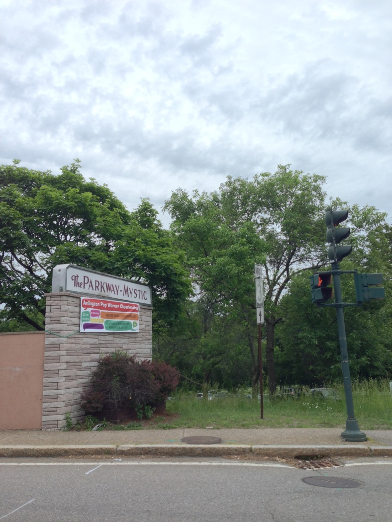 A banner advertising the Arlington Pop Warner Cheerleading program draped across the more permanent sign for the Parkway Mystic apartment building. June 9, 2014.