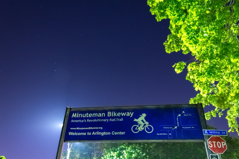 The banner over the Minuteman Bikeway informs cyclists of the route through the oft busy Arlington Center. June 1, 2014.