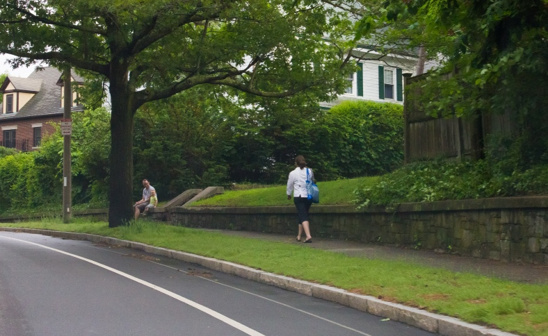 A child is all smiles as his mother walks up the street, home from work for the day. June 10, 2014.