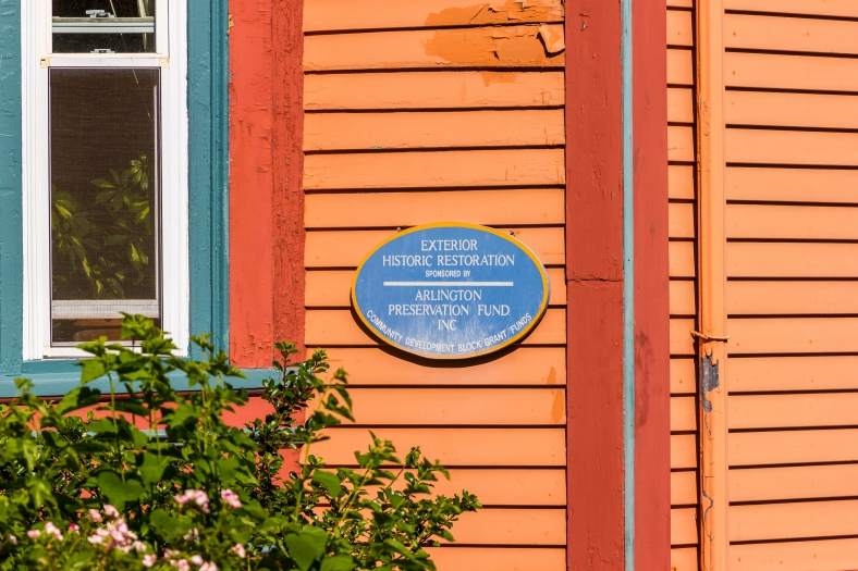 A blue oval plaque on the side of a Teel Street home informing the curious passer by about the restoration work, and who it is sponsored by. June 20, 2014.