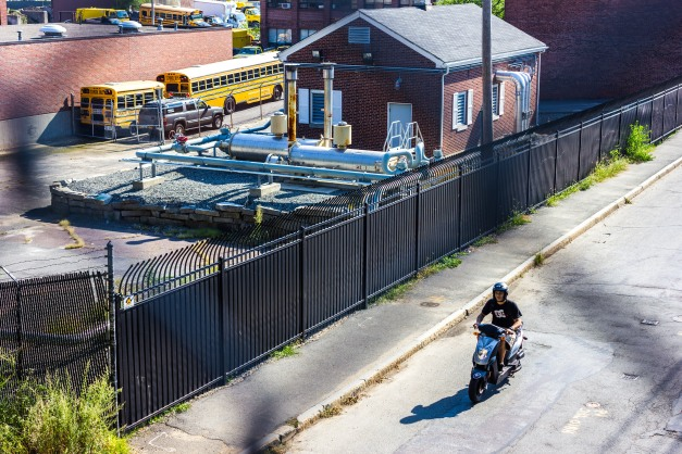 A man cruises down Grove Street on his motorbike past the Department of Public Works yard. September 11, 2013.