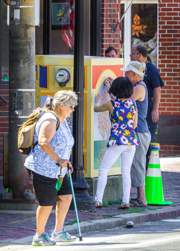 An artist works on her painting, making a colorful attraction of a once drab utility box in Arlington Center. June 27, 2014.