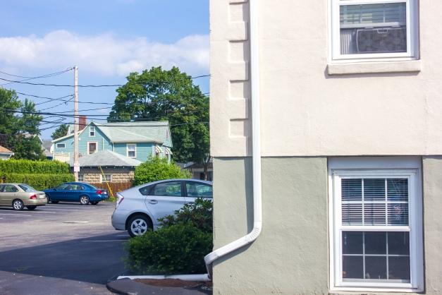 A view of an apartment building, spacious parking lot adjacent, near Arlington Center. July 7, 2014.