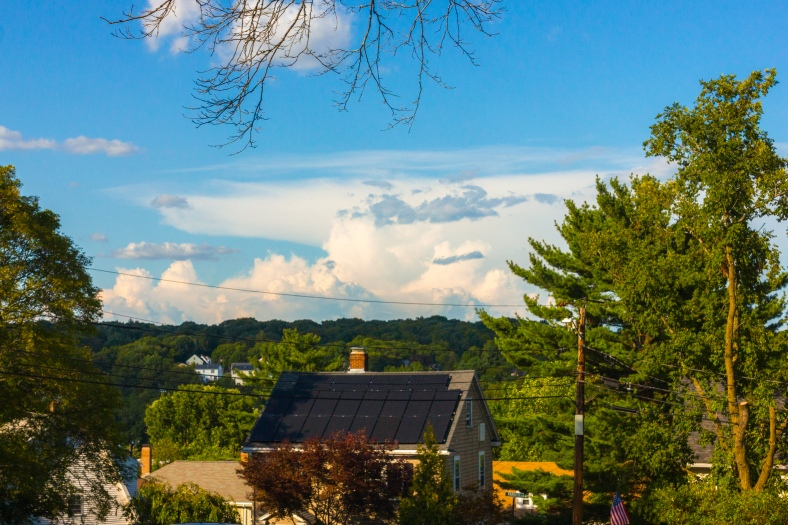 A view of Arlington Heights and the clouds beyond over the solar paneled roof of a Farmer Road home. August 8, 2014.
