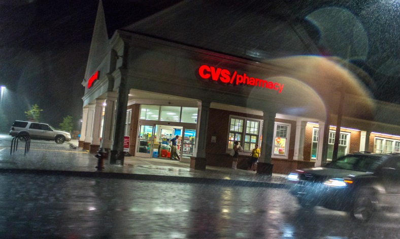 An employee vacuums the entrance of the CVS on Massachusetts Avenue while customers take shelter from a hard rain. August 31, 2014.