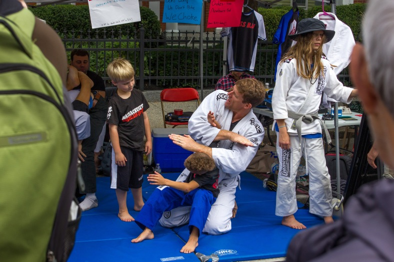 An instructor demonstrates a move at the Brazilian Jiu-Jitsu booth at Town Day. September 13, 2014.