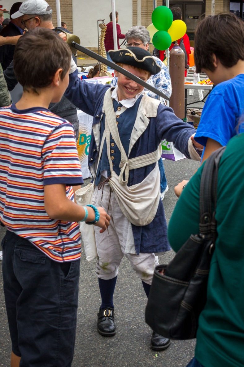 One of the younger members of the Menotomy Minutemen shows off an element of his costume for his friends during Town Day. September 13, 2014.