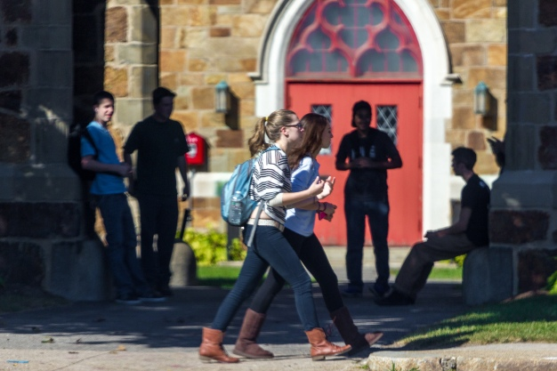 Two girls walk home from school past a group of boys hanging out in the archway of the First Baptist Church of Arlington. September 26, 2014.