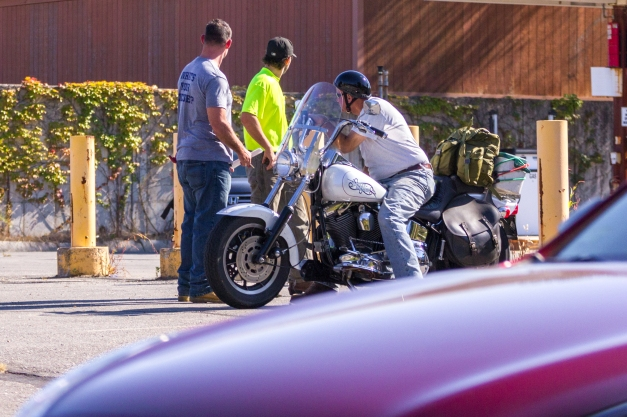 Something catches the eye of three men in the Department of Public Works lot on Grove Street. September 26, 2014.