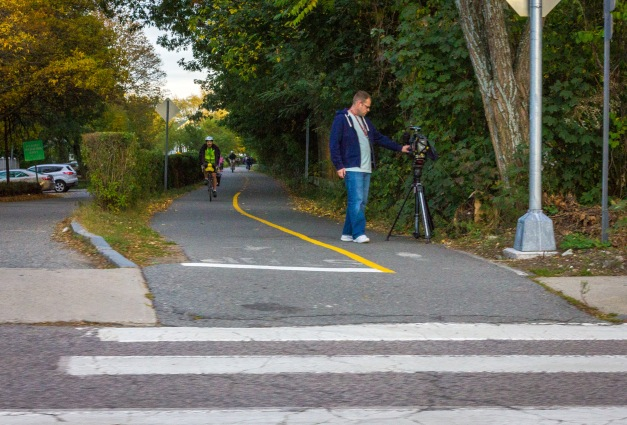 A man stands by his camera set up along the Minuteman Bikeway at the Mill Street crossing. October 10, 2014.