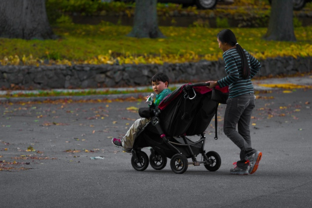 A young boy in a stroller checks to make sure there are no cars coming his way as he is pushed across the street. October 17, 2014.
