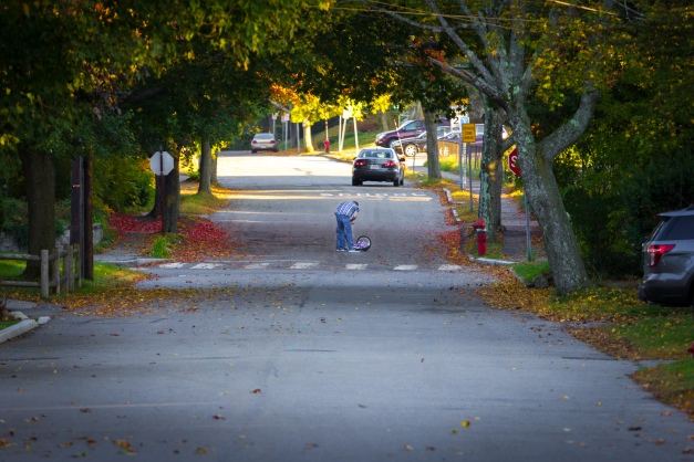 A father helps his young daughter get up after falling off her bike in the middle of the street. October 17, 2014.