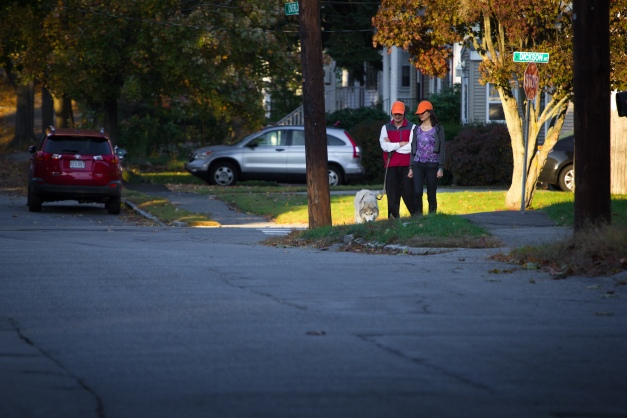 A couple in matching, visibility-boosting hats stop briefly with as their dog takes an interest in something along Overlook Road. October 17, 2014.