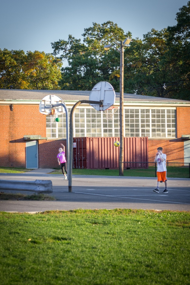 Two children play at two separate basketball hoops at the Stratton School playground. October 17, 2014.