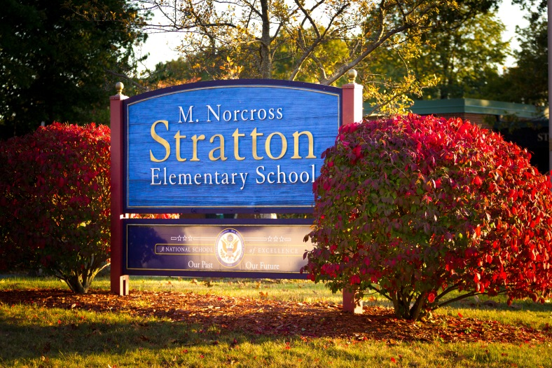 The sign in front of the Stratton School flanked by bushes in shades of Autumn. October 17, 2014.
