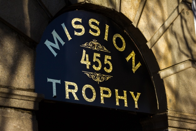 The glittering awning for Mission Trophy over a door squeezed in amongst storefronts on Massachusetts Avenue in Arlington Center. November 29, 2014.