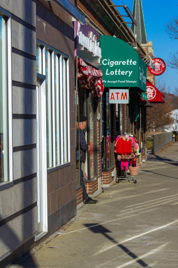 A man stands in the front entrance of a Medford street shop while smoking a cigarette. November 29, 2014.
