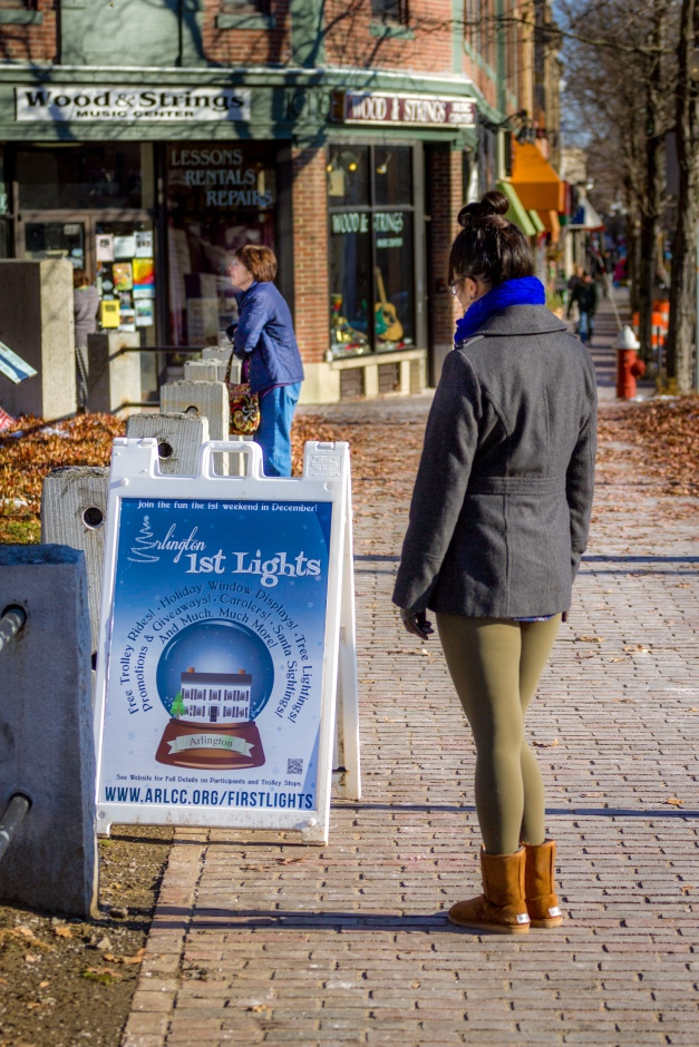 A woman stops to read the Arlington Lights sign while another admires the scene of the Jefferson Cutter House and Whittemore Park. November 29, 2014.
