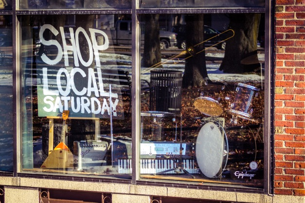A sign in the window of Wood and Strings music store in Arlington Center promoting a local shopping day the day after black Friday. November 29, 2014.