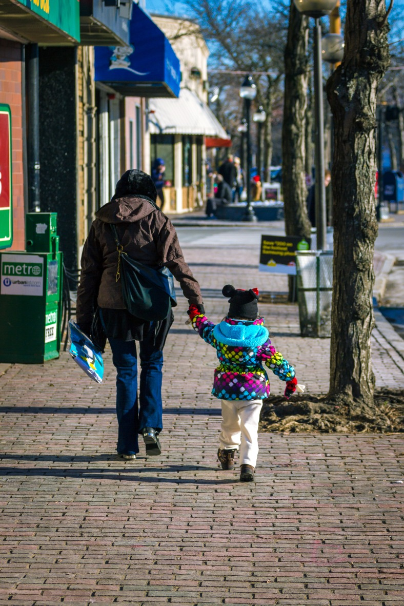 A young girl in a colorful coat walks along Massachusetts Avenue in Arlington Center. November 29, 2014.