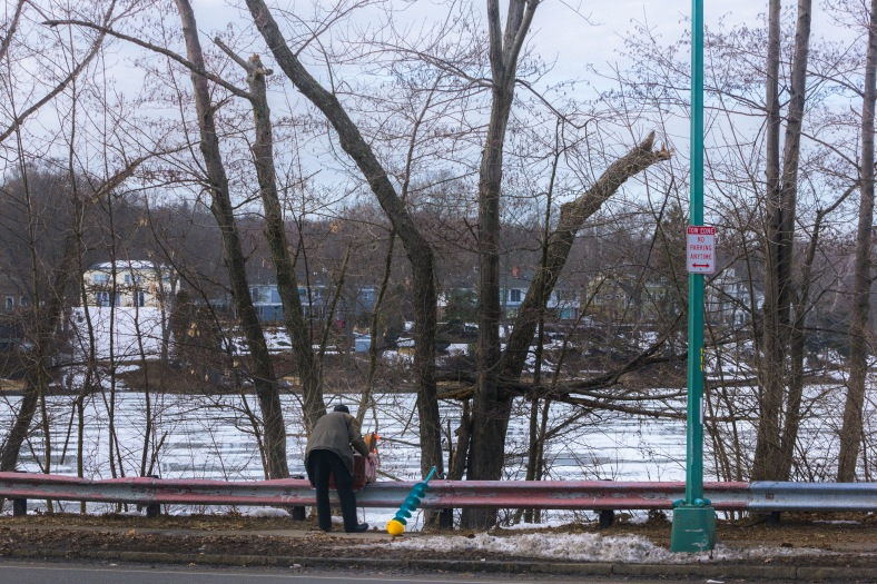 A man on his way to try his hand at ice fishing on the Lower Mystic Lake. March 08, 2014.