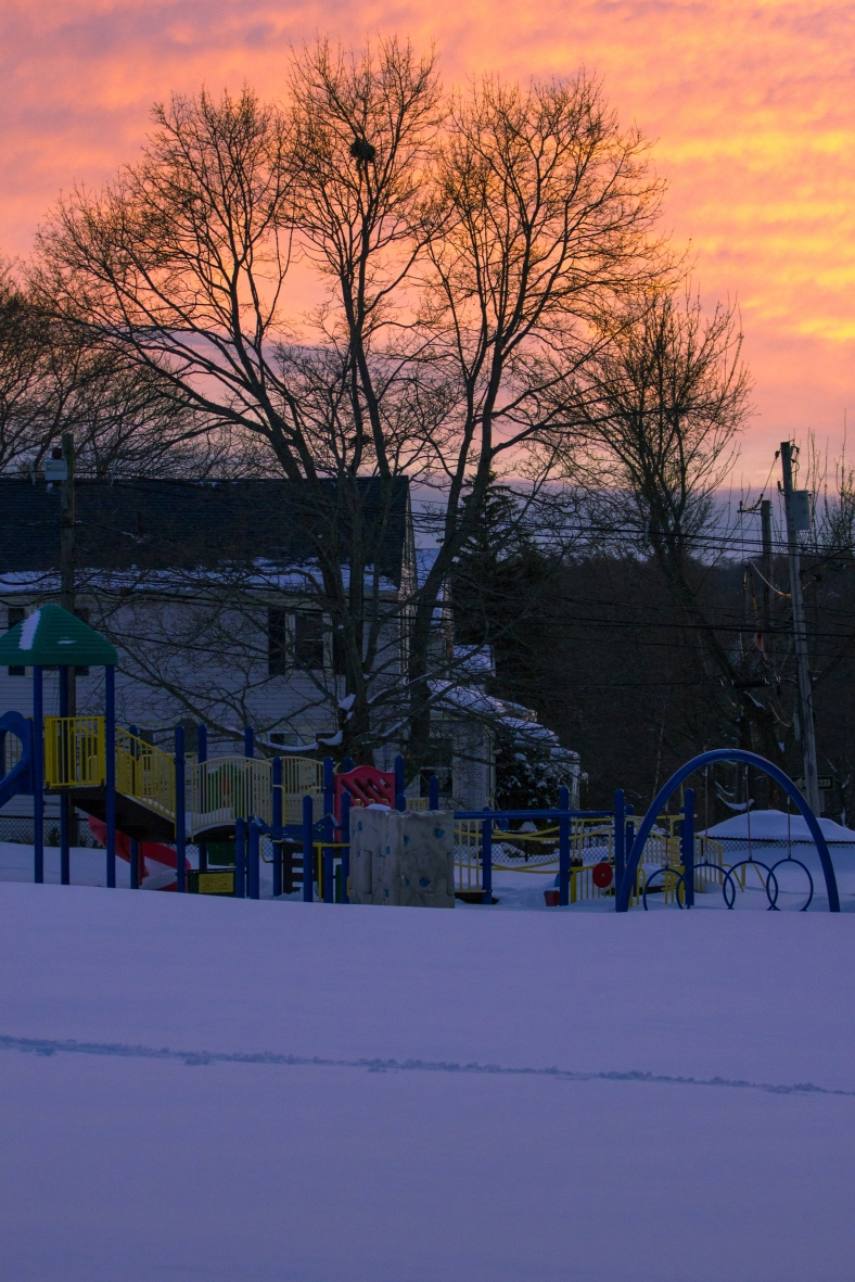 A snowy field and playground under a bright February sunset. February 10, 2015.