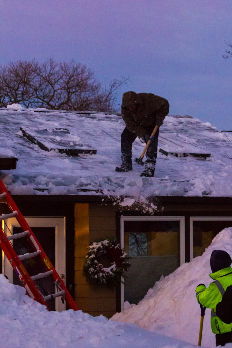 A man uses a sledgehammer to break up an ice dam on a Mountain Avenue home. February 10, 2015.