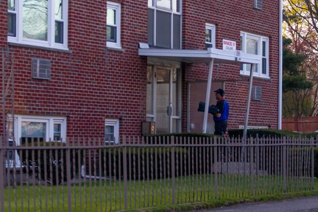 A pizza delivery man waits at the door of an apartment building on Gardener Street. April 28, 2013.