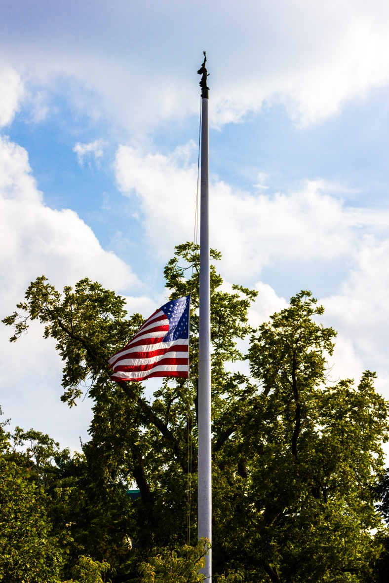 "The flag at half staff on the Town Hall flagpole. The Cyrus Dallin sculpture ""Allegory of Massachusetts"" the finial. September 12, 2013."
