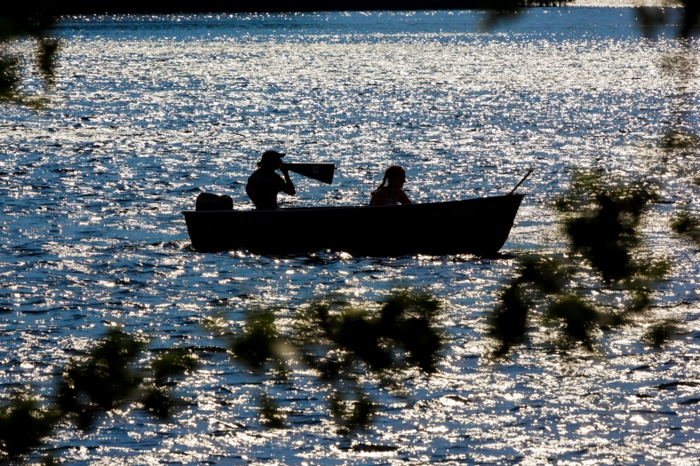 A crew coach shouts instructions through a megaphone during a practice on Spy Pond. September 12, 2013.