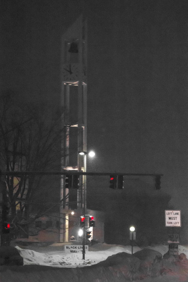 The lights at the main crossroads show all red as snow falls on Arlington Center. March 01, 2015.