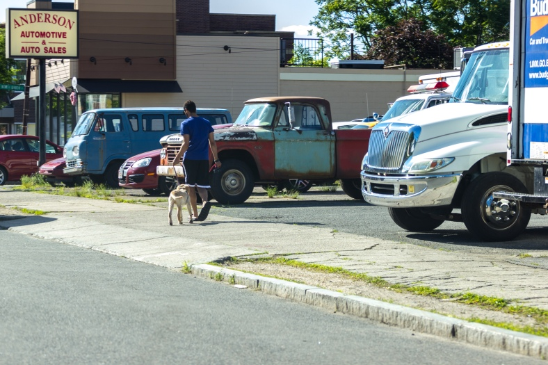 A man walks his dog past Anderson Automotive on Broadway. June 20, 2014.