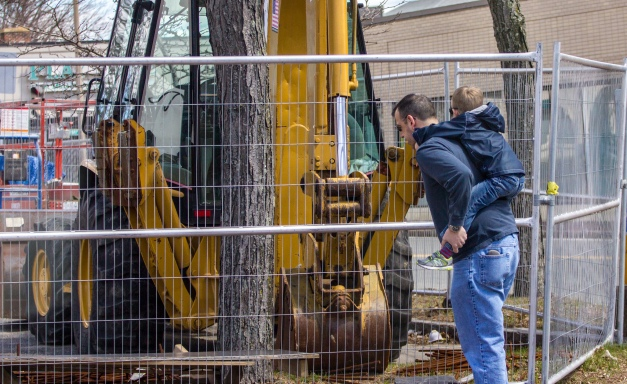 A father stops to let his son take a look at the construction machinery at the Central Fire Station. April 11, 2015.