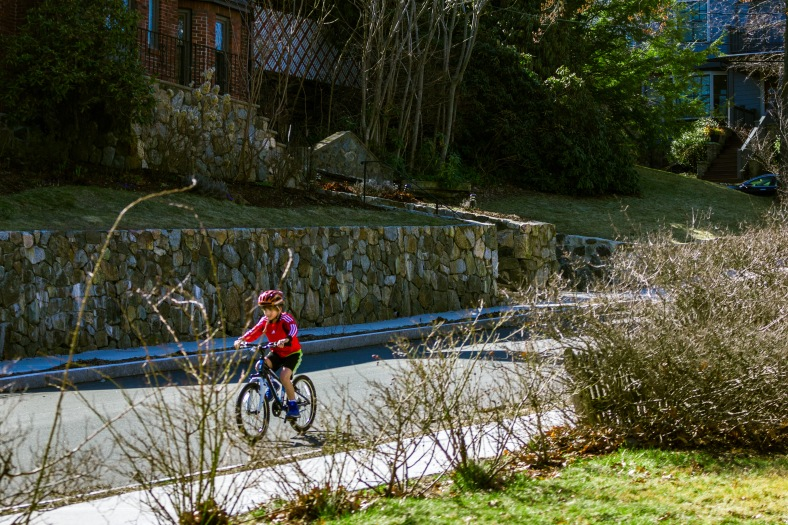 A young boy in red rides his bicycle down Kensington Park toward Pleasant Street. April 11, 2015