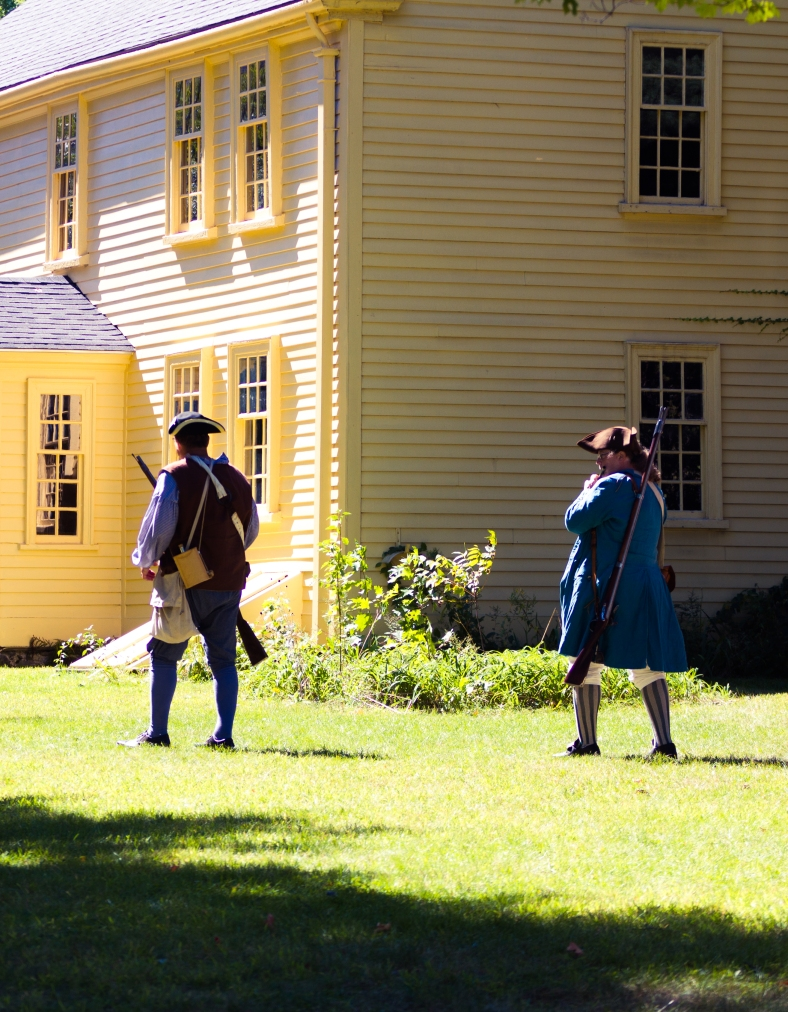 "Menotomy minutemen emerge from ""under the trees at the turn of the road"" to cross the Jason Russell house lawn during Town Day. September 15, 2012."