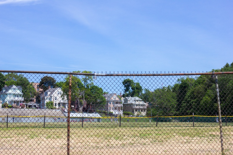 Beyond two fences, a baseball games takes place at Spy Pond field. June 07, 2015.