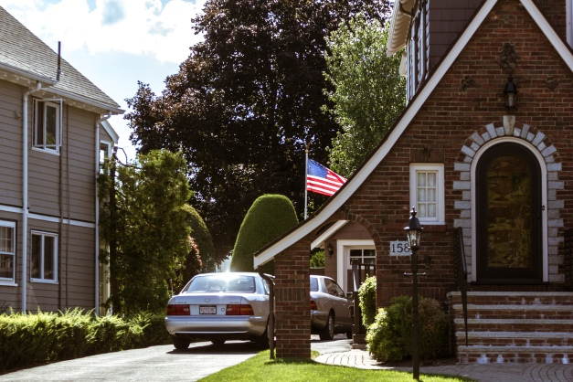 A home, complete with flagpole and American flag, along Mystic Street. August 05, 2015.