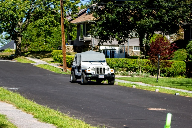 A Jeep, covered from the elements (in this case the sun,) on a newly paved Upland Road. August 05, 2015.