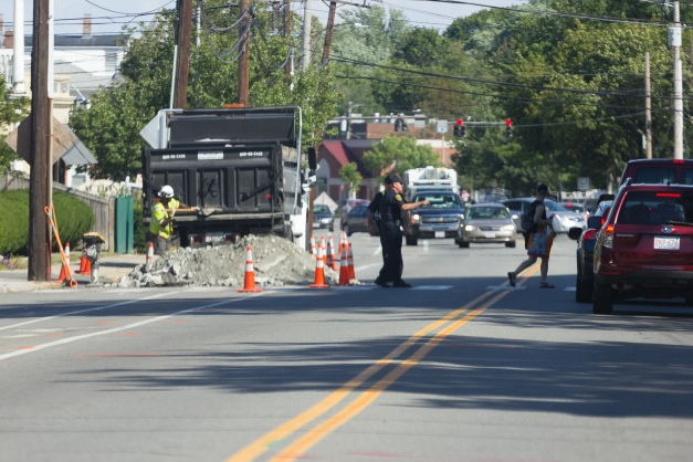 A police officer aids a pedestrian in crossing Massachusetts Avenue near a road work site. August 05, 2015.