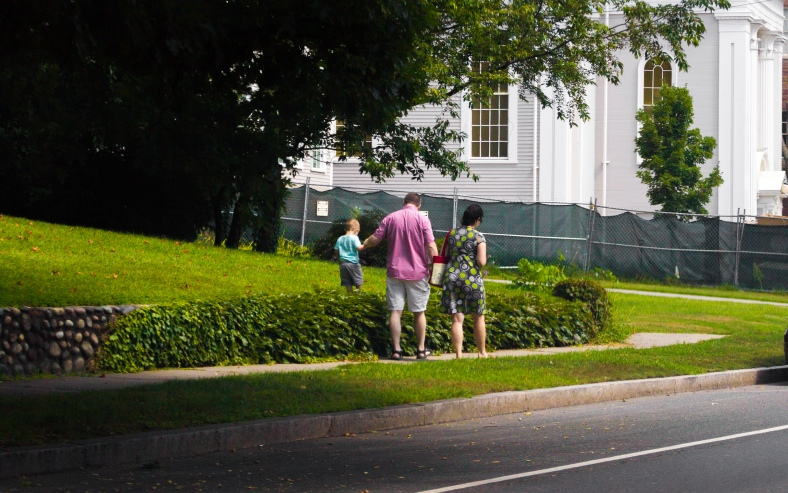 A toddler walks on a stone wall alongside his parents down Pleasant Street. August 29, 2015.