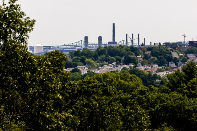Smokestacks and the Tobin bridge create the horizon behind the Tufts campus in Medford as seen from Hattie Symmes Park. August 29, 2015.