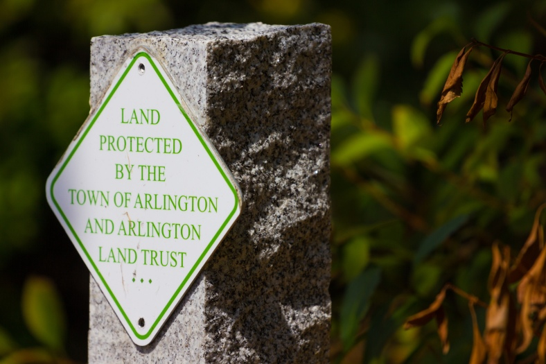 A granite pylon marks land protected by the Arlington Land Trust along Summer Street. August 29, 2015.