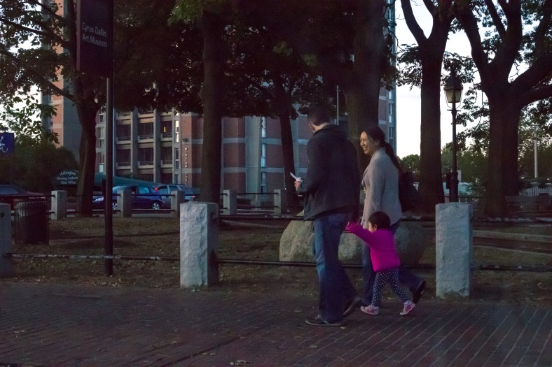 A family enjoying a walk in Arlington Center at twilight. September 26, 2015.