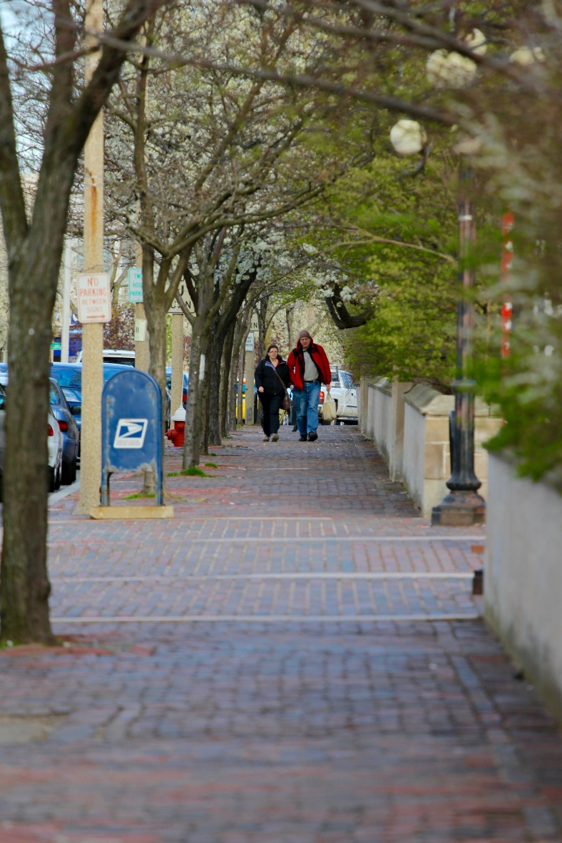 A couple walks down Massachusetts Avenue along the wall of the Winfield Robbins Memorial Garden. April 4, 2012.