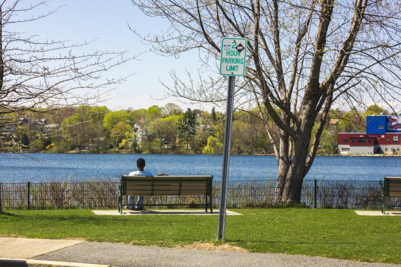 A young man sits on a bench at Spy Pond Park. April 26, 2013.