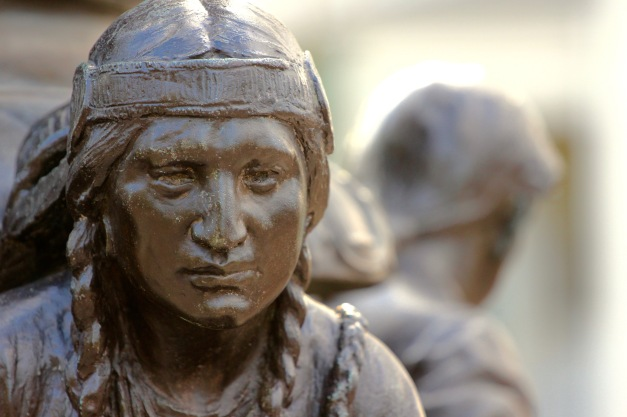 Cyrus E. Dalin's depiction of Squaw Sachem, resident of the land before the village of Menotomy was established, on the flagpole base in the Town Hall garden. April 4, 2012.