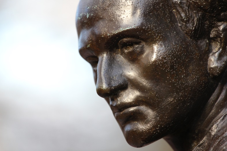 A detail of the face of a Minuteman—one of four figures—at the base of the Robbins memorial flagpole, sculpted by Cyrus E. Dallin. April 4, 2012.