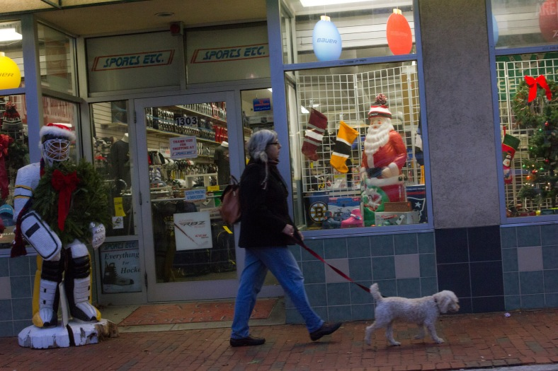 A woman walks her dog past Sports Etc.—decked out for the holidays— in Arlington Heights. December 14, 2015.